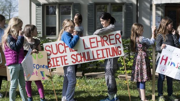 Kinder protestieren mit Transparenten gegen eine Schulleitung