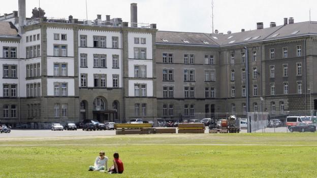 Kaserne, graue Steingebäude. im Vordergrund grüne Wiese mit zwei Personen.