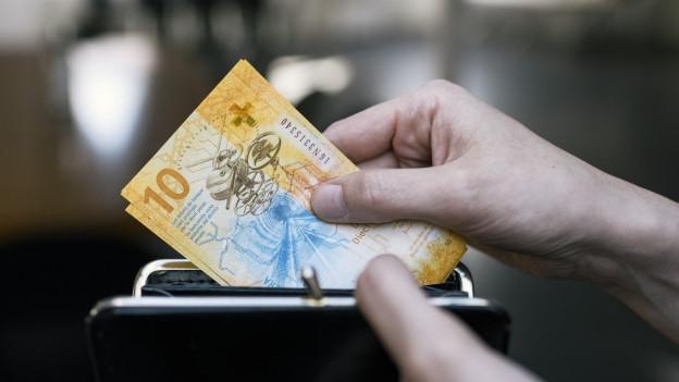 Eine Hand zieht eine Zehner-Note aus dem Portemonnaie.