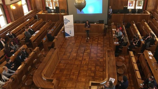 Der Ratssaal von oben, wenige Menschen sitzen in den Reihen