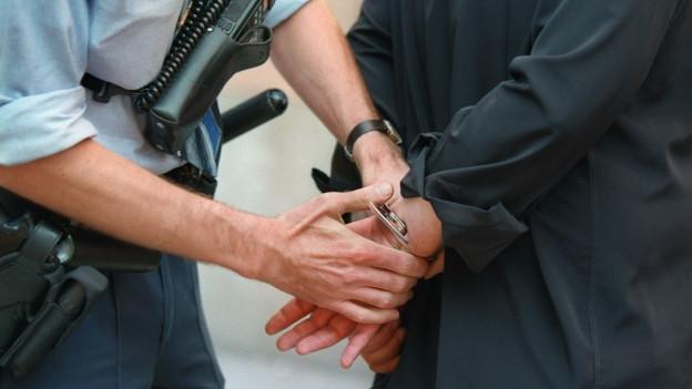 Ein Polizist legt einem mutmasslichen Straftäter Handschellen an.