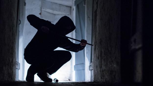 Ein Einbrecher will durch ein Fenster in ein Haus einsteigen.