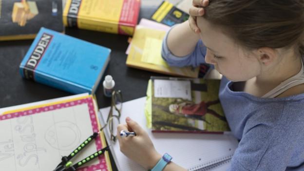 Mädchen am lernen, mit vielen Büchern auf dem Tisch