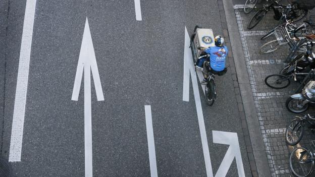 Ein Fahrradfahrer auf einer Strasse, von oben fotografiert.