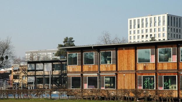 Ein Schulhaus-Pavillon aus Holz, dahinter ein Hochhaus