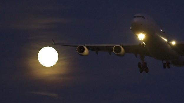 Ein Flugzeug in der Nacht bei Mondschein.