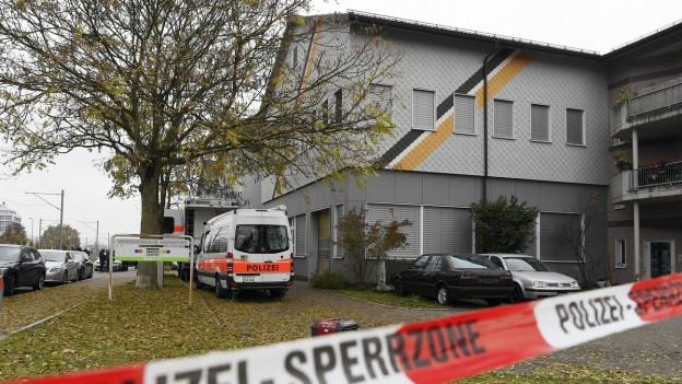 Ein Haus, davor eine Polizeiabsperrung.