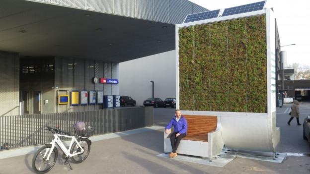 Ein Mann sitzt auf einer Bank vor einer grünen Wand mit Solarpanels obendrauf.