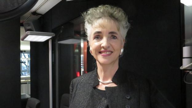 Eine Frau in schwarzem Deux-Pièces steht vor dem Mikronfo.