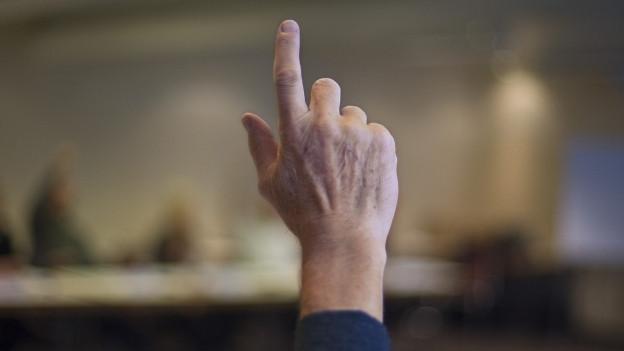 Ein Mann hält einen Finger in die Höhe und will damit das Wort erhalten.