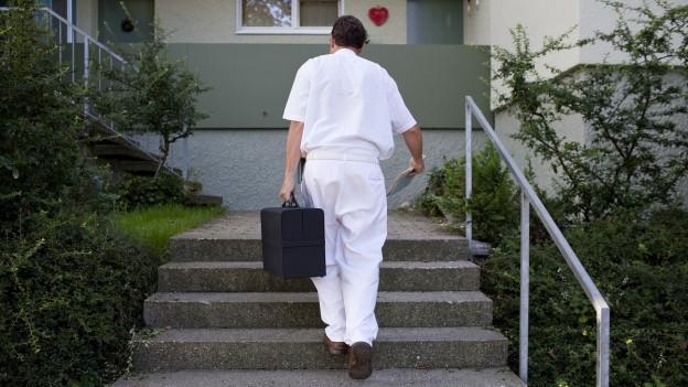 Ein Arzt auf Hausbesuch läuft eine Treppe hinauf zu einer Wohnung.