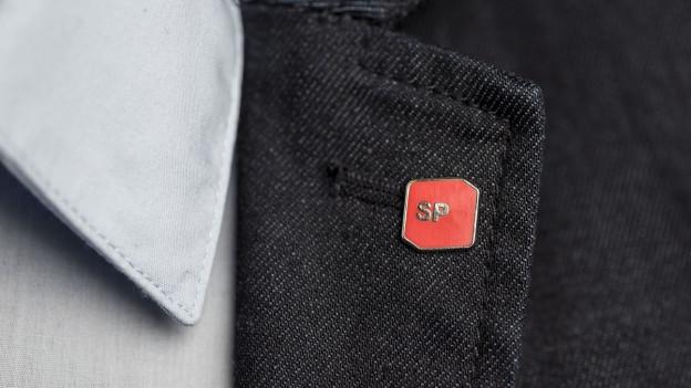 Ein SP-Mitglied hat einen SP-Pin an seiner Jacke.