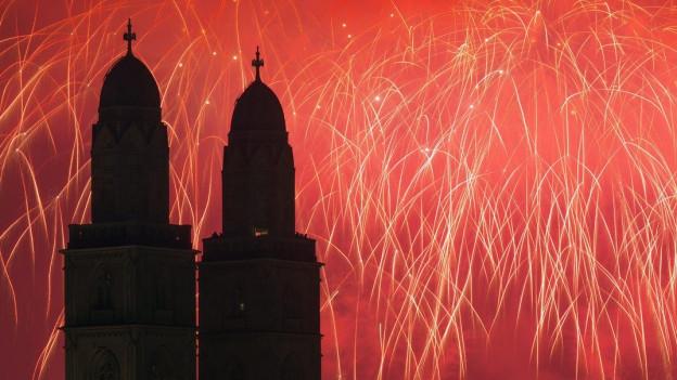 Hinter der Zürcher Kirche Fraumünster leuchtet Feuerwerk am Himmel.