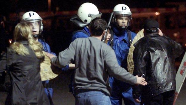 Aufgebrachte Menschen stehen vor Polizisten in Kampfmontur.