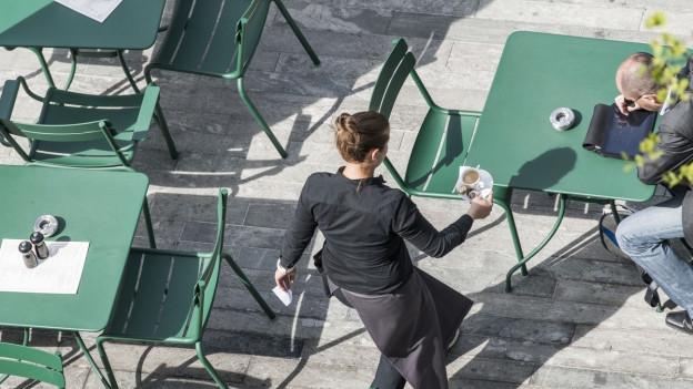 Eine Gartenwirtschaft mit grünen Stühlen und eine Kellnerin serviert einen Kaffee.