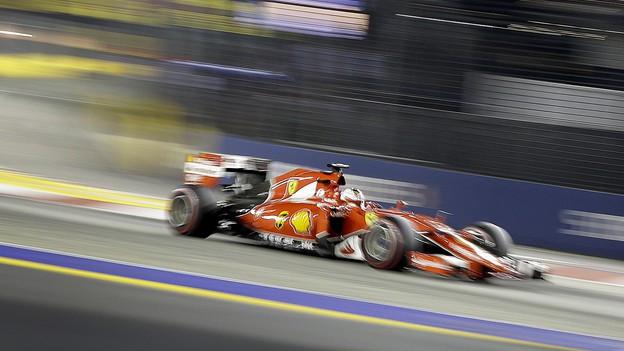 Ein rotes Rennauto flitzt über eine Strasse
