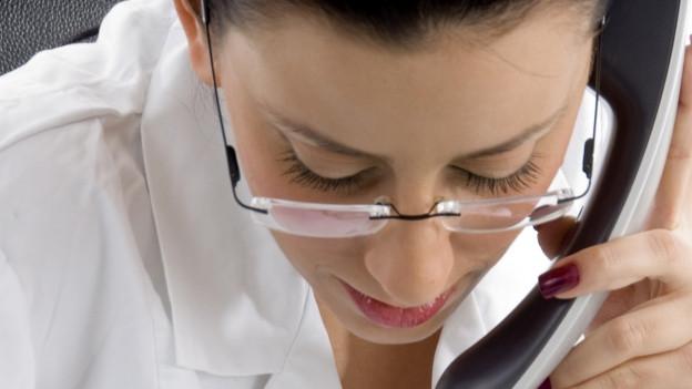 Eine Ärztin hört am Telefon zu und macht Notizen