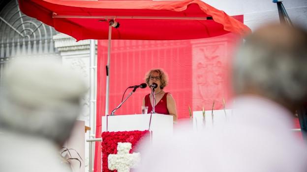 Eine Frau am Rednerpult spricht in zwei Mikrofone.