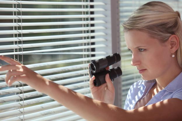 Eine Frau mit Videokamera blickt durch eine Jalousie