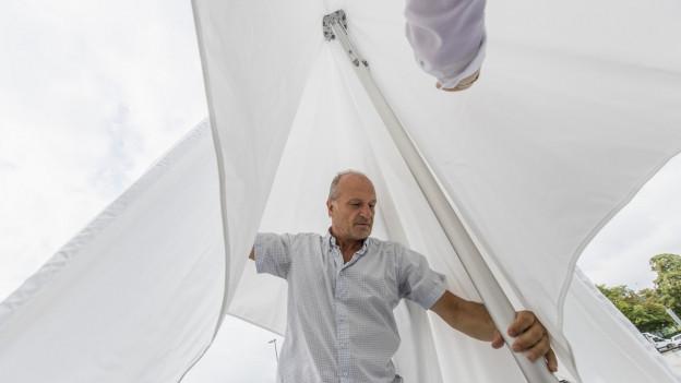 älterer Mann öffnet grossen weissen Sonnenschirm
