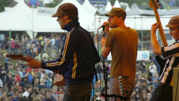 Eine Musikband auf einer Open-Air Bühne und das Publikum
