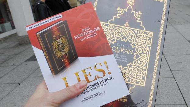 """Eine Hand hält einen Koran und eine Broschüre der Aktion """"Lies!"""""""