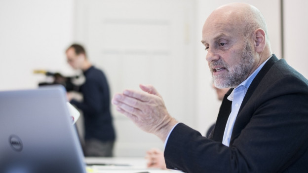 André Odermatt an einem Tisch vor einem Computer bei einer Präsentation.