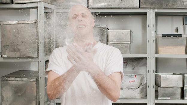 Ein Mann klatscht in die Hände, Mehl stäubt.