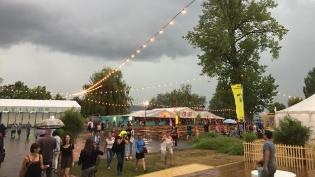 Dunkle Wolken überschatten das Zürcher Theaterspektakel, Menschen verlassen das Gelände.