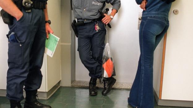 Polizisten begleiten eine Prostituierte zum Verhör.