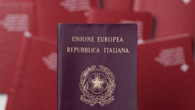 Ein italienischer Reisepass vor einen Haufen Schweizer Pässe