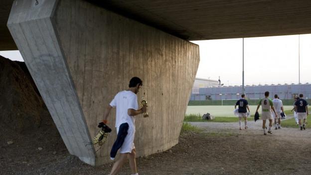 Eine grosse Betonsäule vor einem Sportplatz und ein Fussballspieler der auf den Rasen geht.