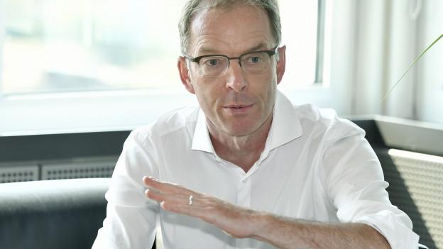 Portrait Daniel Leupi mit Geste, die Anstieg anzeigt.