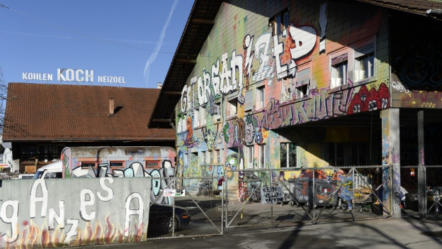 """Mauern und Häuser mit Graffiti, im Hintergrund auf einem Dach der Schriftzug """"Kohle - Koch - Heizöl"""""""
