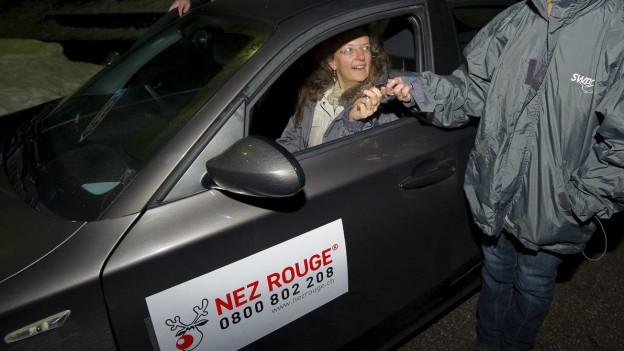 Eine Frau übergibt einer Nez Rouge-Fahrerin ihren Autoschlüssel.