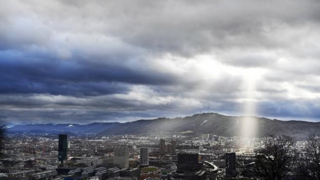 Blick auf Zürich, darüber viele Wolken, die Sonne bricht durch.