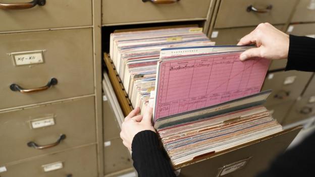 Eine Akte wird aus einem riesigen Aktenschrank gezogen.