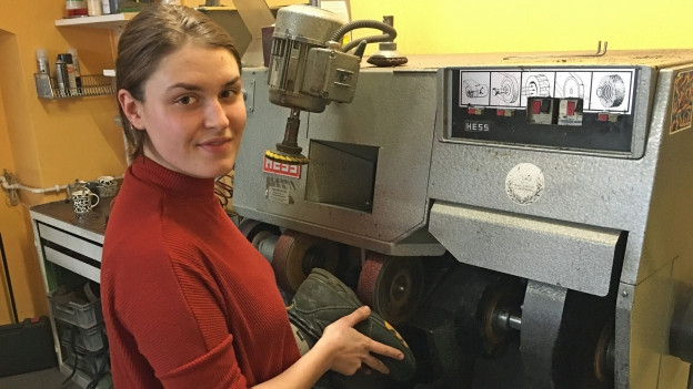 Schuhmacherin Raissa Zimina schleift an einer Maschine die Sohle eines Wanderschuhs ab.
