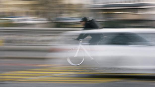 Ein Auto und ein Velo flitzen über einen Fussgängerstreifen (unscharf)