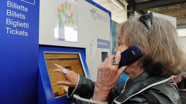 Eine Frau holt sich vor dem ZVV-Billettautomat telefonisch Hilfe.