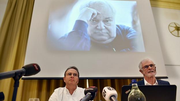 Zwei Männer hinter Mikrofonen, oben das Bild von Jürg Jegge auf die Wand projieziert.