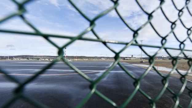 Blick durch einen Zaun auf die Pisten des Flughafens Zürich