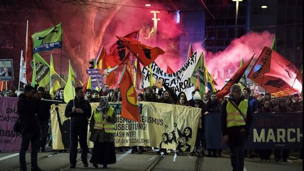 Ein Demonstration gegen das WEF mit Fackeln und Bannern