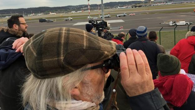 Mann mit grauen Haaren und Kappe schaut mit Feldstecher richtung Flughafen.