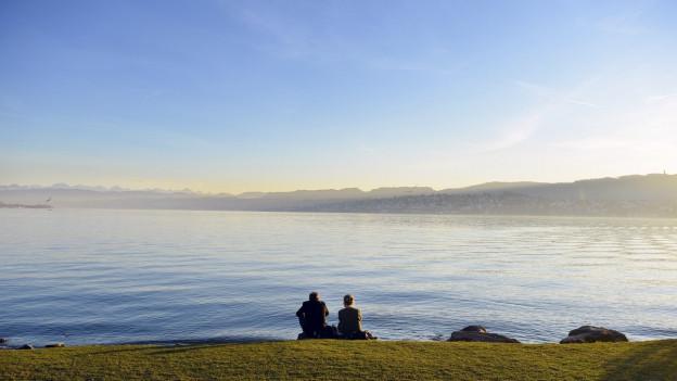 Ein Paar sitzt am Ufer des Zürichsees.