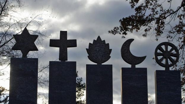 Fünf Stehlen mit den Symbolen der fünf Weltreligionen.