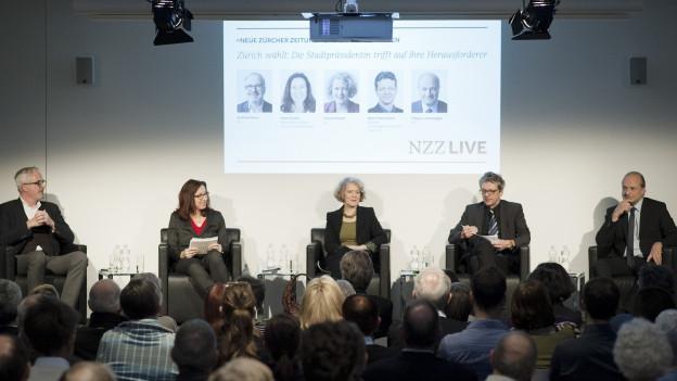 Zwei Frauen und drei Männer sitzen auf einem Podium.