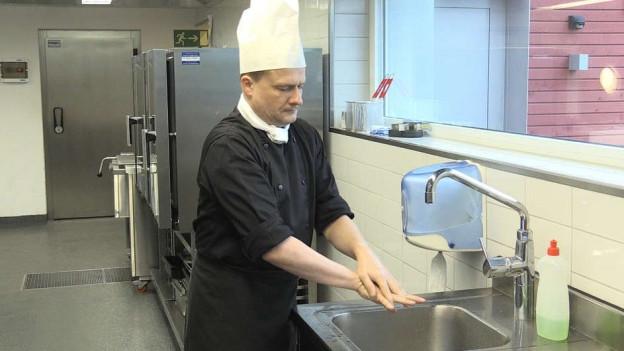 Ein Mann steht an einer Spühle und wäscht sich die Hände.