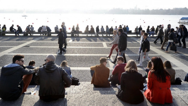 Viele Menschen sitzen am Ufer des Zürichsees an einem sonnigen Wintertag.