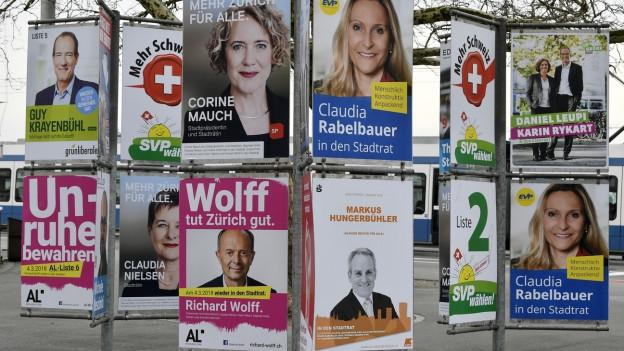Eine Wand beklebt mit Plakaten von verschiedenen Kandidatinnen und Kandidaten
